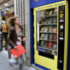 A passer-by runs past a book vending machine in a street of Paris, Friday, Aug. 19, 2005. Parisians craving Homer, Baudelaire or Maupassant in the middle of the night can get a quick literary fix at one of the French capital's five newly-installed book vending machines. Headline on the machine reads: 'Book anytime'.