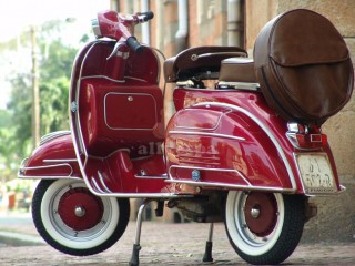 A beautifully restored red Vespa scooter